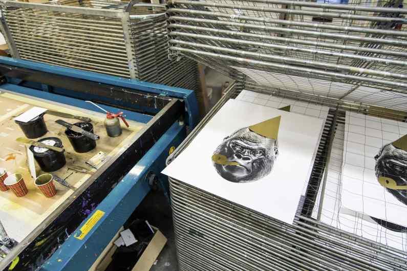 Multiple small Big Bang screen prints in a drying rack - Big Bang (edition, black, gold leaf, framed, screen print), 2016 by Joseph Klibansky